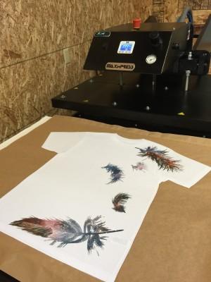 Original Custom Cosmic Feathers Design on All Over Shirt next to Heat Press