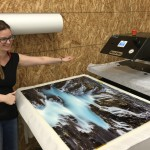 Rhiannon pulling an Art Wolfe metal print from the press