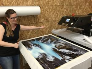 Rhiannon pulling an Art Wolfe metal print from the press