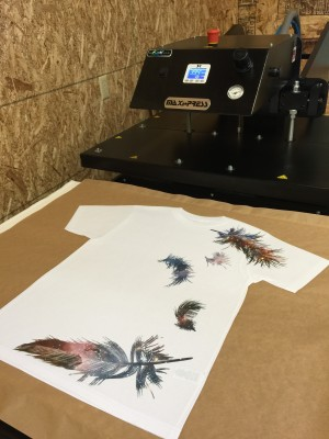 Original Custom Cosmic Feathers Design on All Over Shirt next to Heat Press